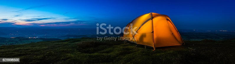 Warmly illuminated dome tent pitched on a picturesque mountain top wild camp site overlooking lights in the valley far below at sunset.