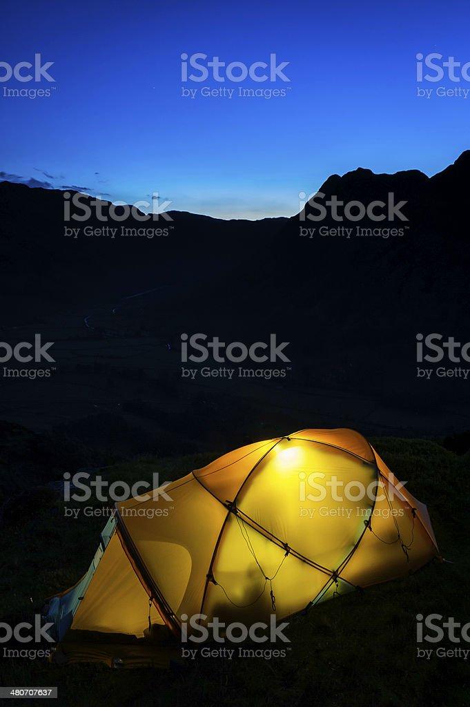 Warmly illuminated tent pitched high on dark dusk mountain peak royalty-free stock photo