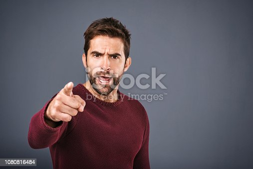 Studio shot of a handsome young man pointing a finger in anger against a gray background