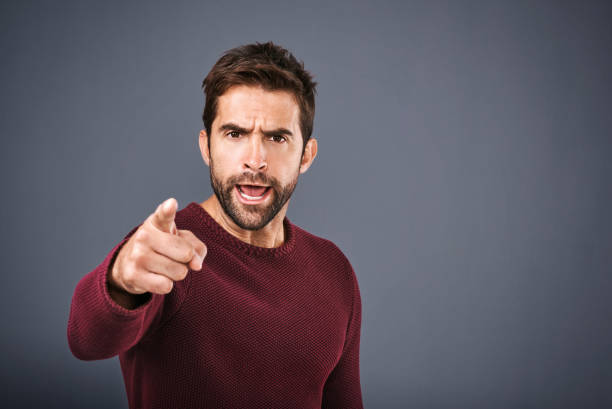 I warned you that would happen! Studio shot of a handsome young man pointing a finger in anger against a gray background agitation stock pictures, royalty-free photos & images