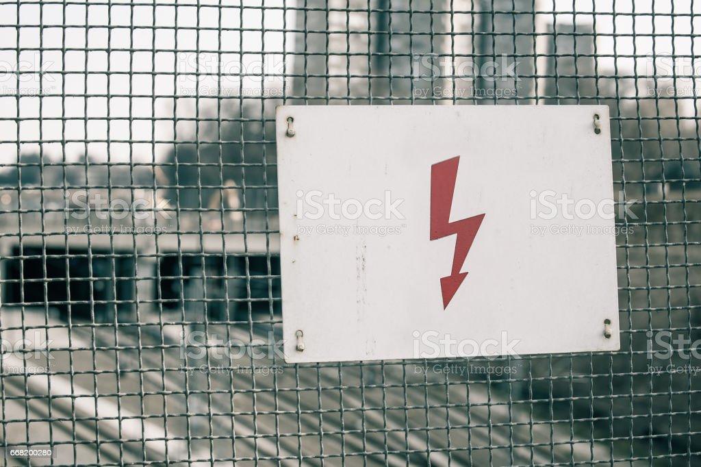 Um sinal elétrico de perigo aviso em cima do muro - foto de acervo