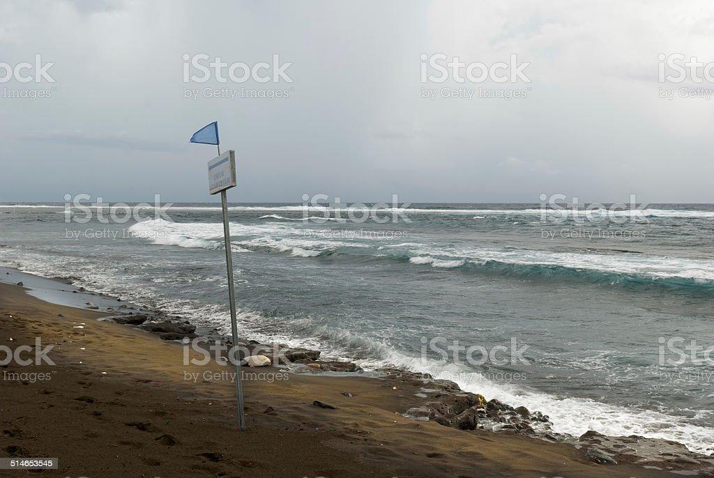 Warning flag pole on the beach stock photo