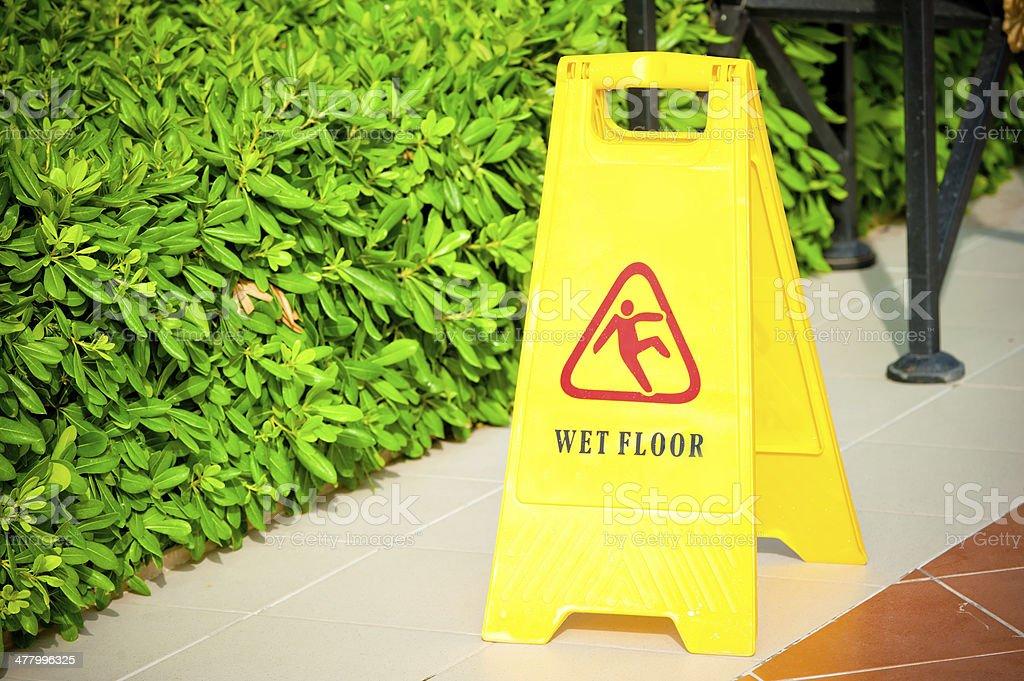 warning label 'Wet floor' yellow on the tile floor stock photo