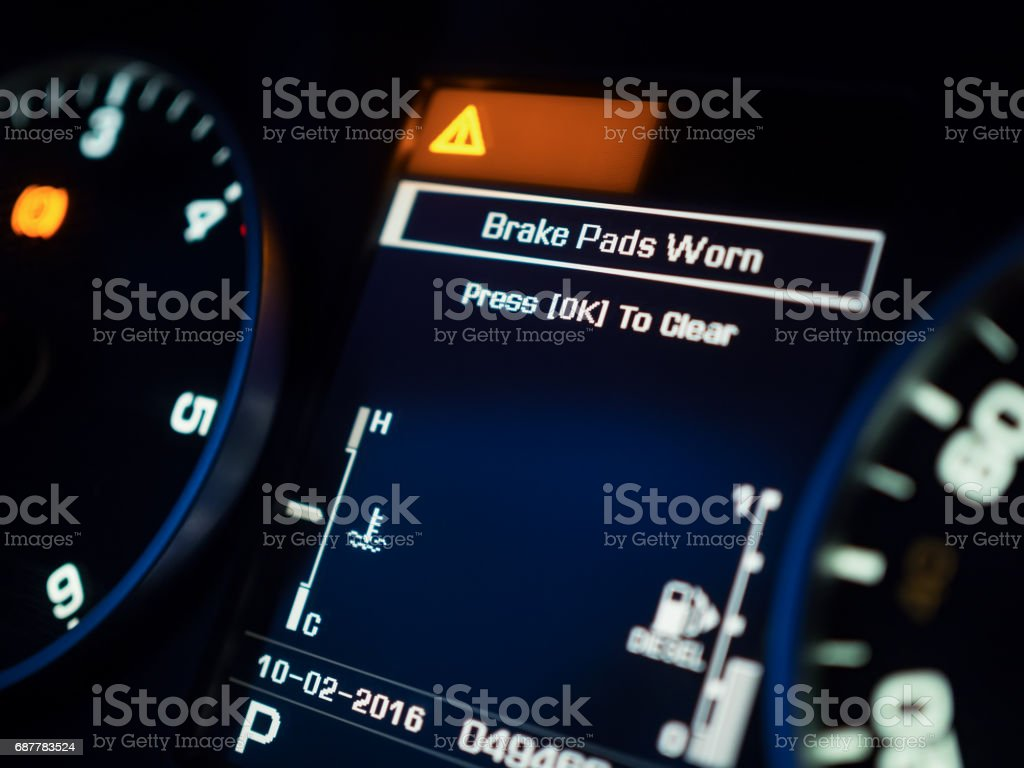 Warning of brake pad wear on a dashboard, shallow depth of field stock photo