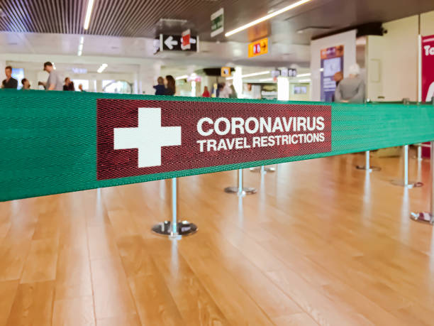 Warning of travel restriction in airport Green ribbon barrier inside an airport with the warning of travel restrictions due to the spread of the dangerous Coronavirus forbidden stock pictures, royalty-free photos & images