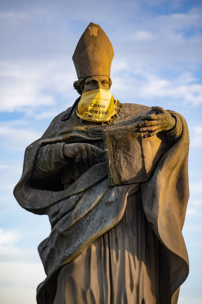COVID warning on statue St Bruno of Wurzburg stock photo