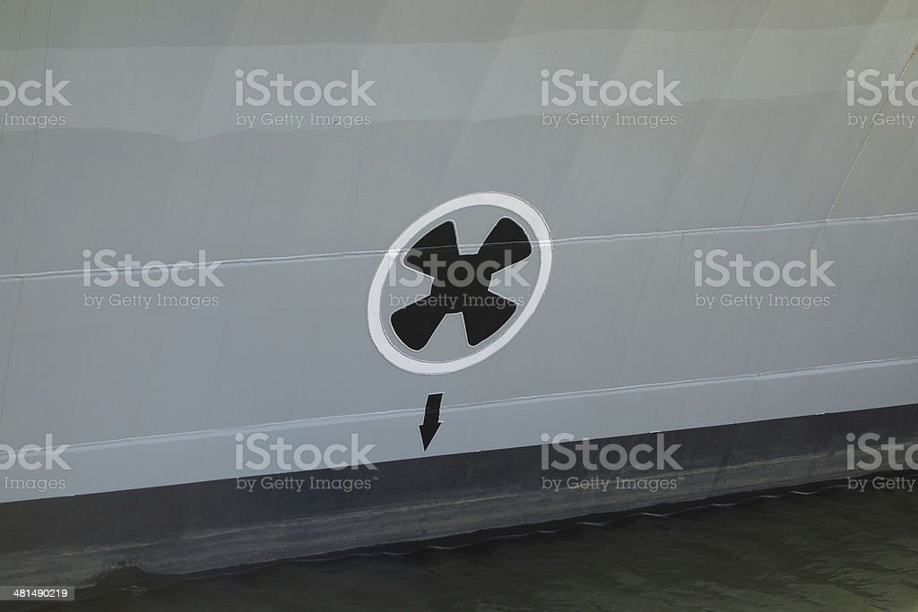 warning propeller below water level on side of navy ship stock photo