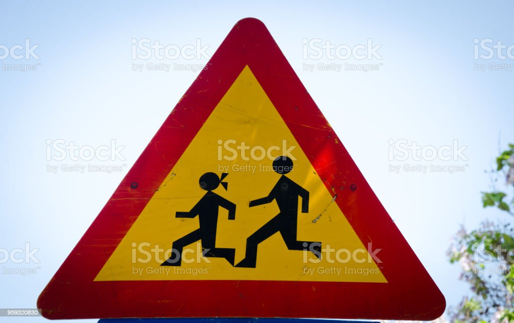 Warning school sign with school children running isolated on blue sky...
