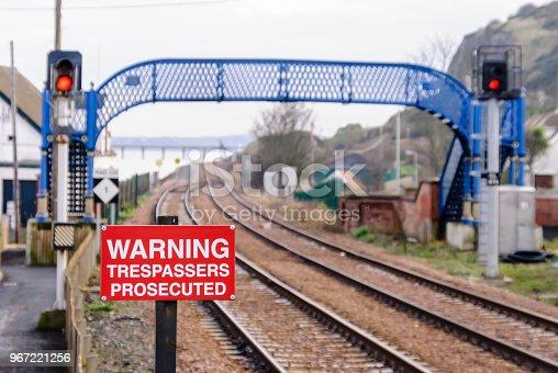 Warning sign and a pedestrian footbridge over railway tracks.