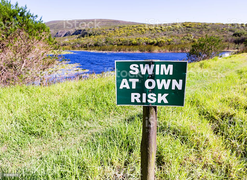 Warning sign at dam: Swim at own risk stock photo