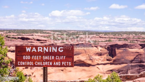 Canyon de Chelly national monument, Arizona, US. Warning sign, sheer cliff, control children and pets text, sunny spring day, blue sky with clouds