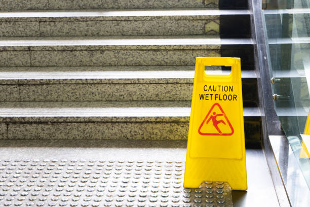 warning sign for wet floor near the stair - cadere foto e immagini stock