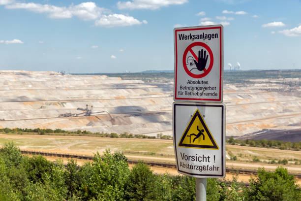 Warning sign near open pit mine Hambach in Germany Warning sign near open pit mine Hambach with brown coal digging in Germany tagebau stock pictures, royalty-free photos & images