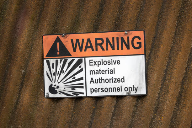 Warning sign on a corrugated iron wall with the inscription: explosive material authorized personnel only Warning sign on a corrugated iron wall with the inscription: explosive material authorized personnel only explosive stock pictures, royalty-free photos & images