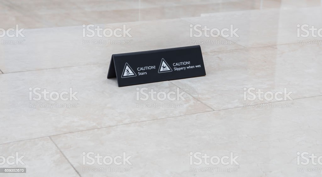 Warning sign slippery and stairs on marble floor background stock photo