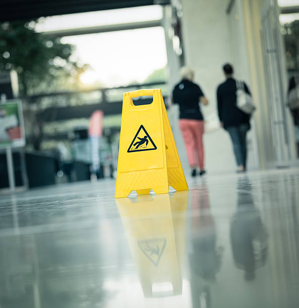 """Warning sign slippery A yellow warning sign """"slippery """" with walking people in the background slippery stock pictures, royalty-free photos & images"""