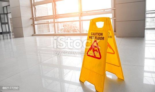 Yellow sign on floor that alerts for wet floor.