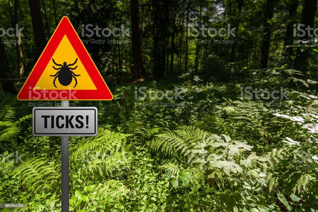 """Um sinal de aviso """"Tiques"""" na floresta - Foto de stock de Alemanha royalty-free"""