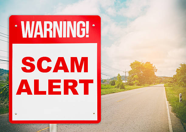warning sign warning about Scam in road ahead. stock photo