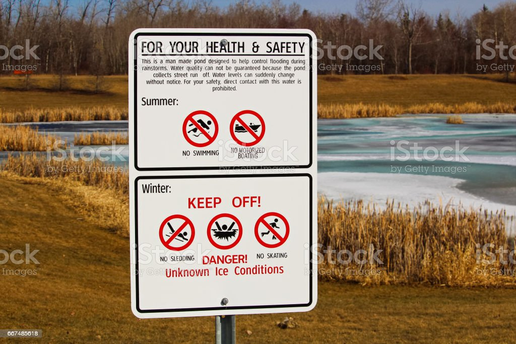 Warning signs around storm drainage pond stock photo