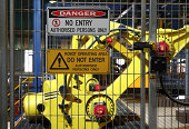 Warning signs outside robotic assembly line with robot in background