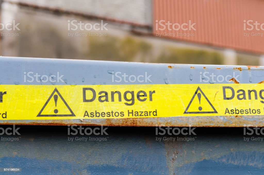 Warning tape across a bin at an Asbestos clean-up stock photo