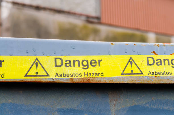 Warning tape across a bin at an Asbestos clean-up - foto stock