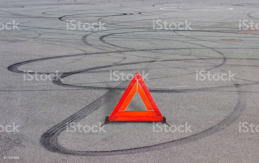 Warning triangle and tire tracks on asphalt stock photo