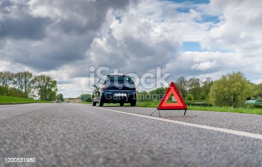 A warning triangle in front of a car with a breakdown
