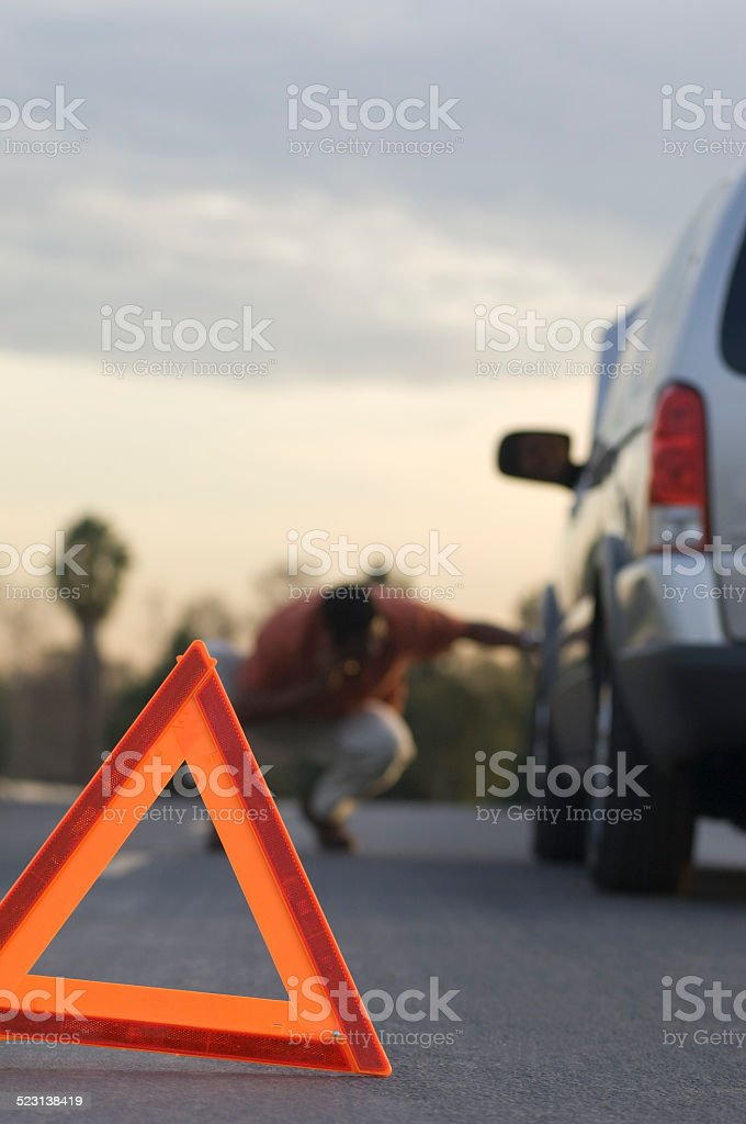 Warning triangle in front of broken down car stock photo