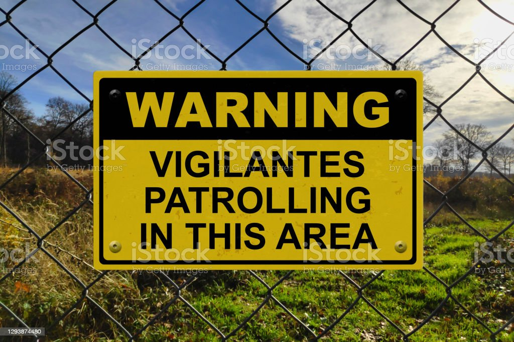 """Warning - Vigilantes patrolling in this area Black and yellow warning sign on a fence stating in """"Warning - Vigilantes patrolling in this area"""". Black Color Stock Photo"""