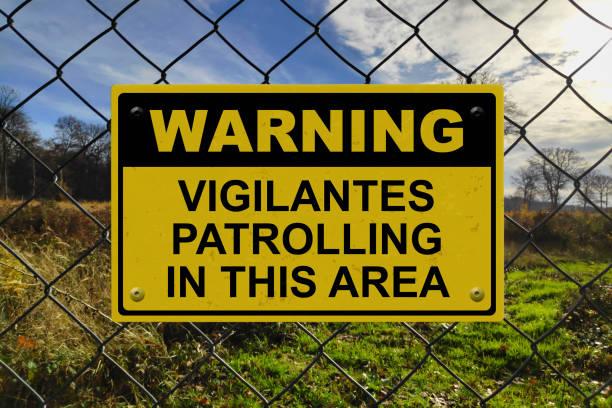 Warning - Vigilantes patrolling in this area stock photo