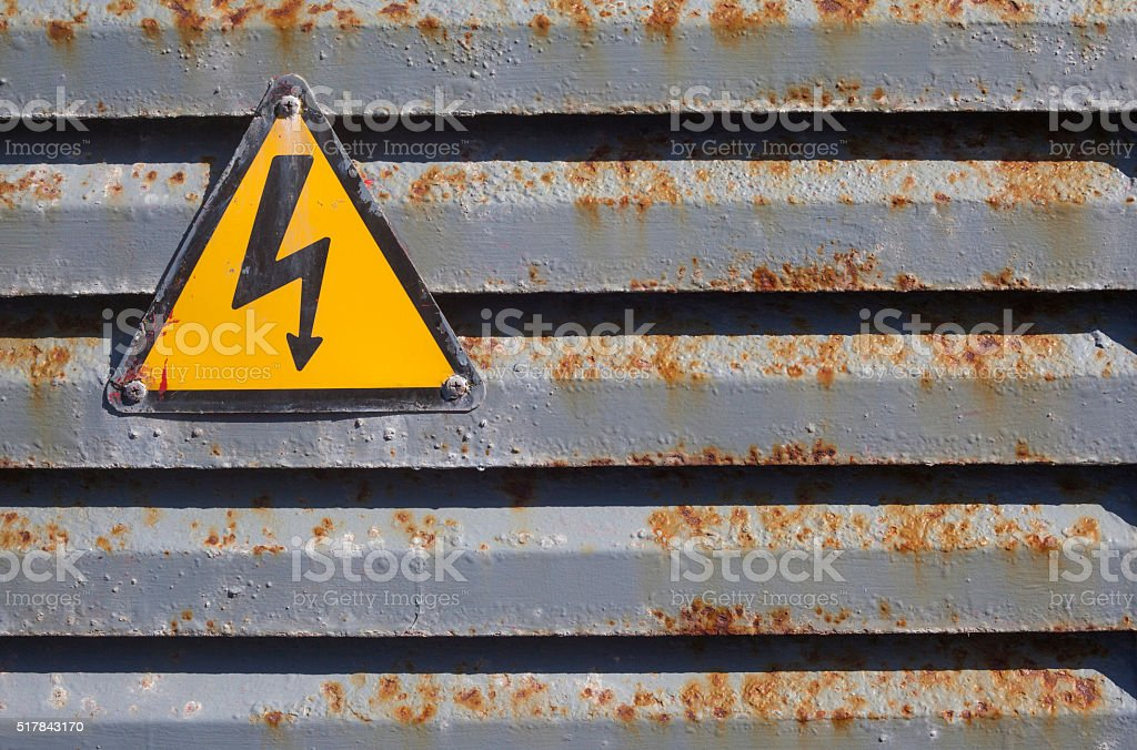 Warning voltage icon on a rusted structure stock photo