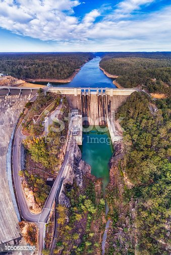 Massive concrete Warraganba dam on Warragamba river forming catchment area to supply fresh water to Greater Sydney - aerial panorama.