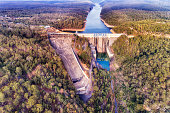 Renewable energy generation by Warragamba dam on Nepean river in the Greater Sydney - dam shutter gate forming lake in elevated aerial view.