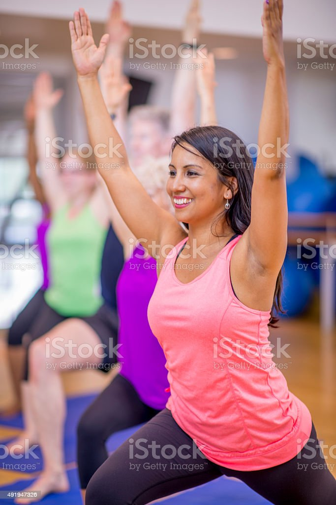 Warrior 1 Pose in Yoga Class stock photo