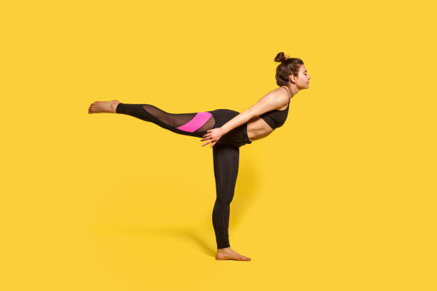 Warrior 3 pose. Slim woman with hair bun in tight sportswear practicing yoga, doing Virabhadrasana Warrior 3 pose. Slim woman with hair bun in tight sportswear practicing yoga, doing Virabhadrasana III exercise on one leg, stretching muscles and balancing. studio shot, sport workouts isolated yogi stock pictures, royalty-free photos & images
