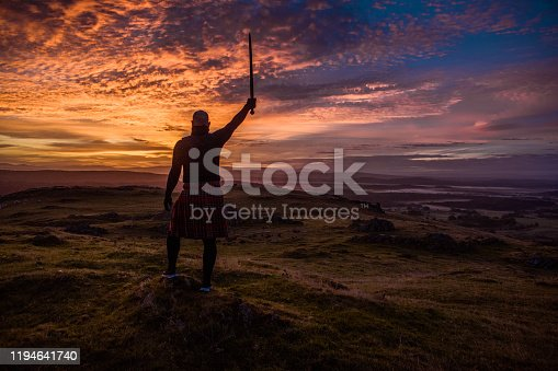 A Warrior Angel holding a sword overlooking beautiful British landscape at dawn