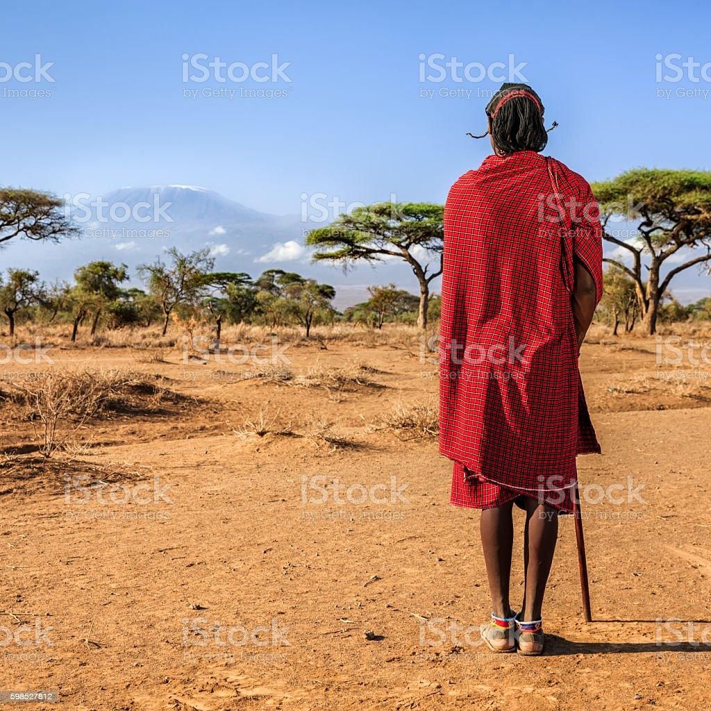 Warrior from Maasai tribe looking at Mount Kilimanjaro, Kenya, Africa stock photo