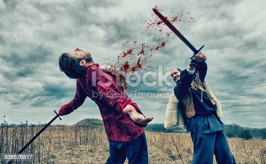 istock Warrior kills opponent with sword on a battlefield 538876517