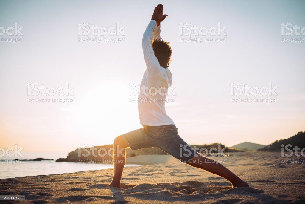 Krieger-Pose am Strand im Sonnenuntergang – Foto