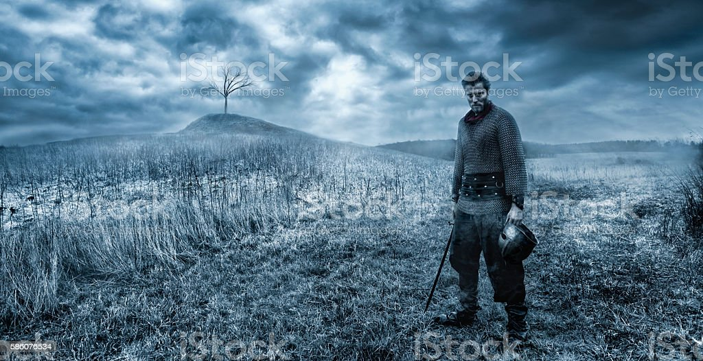 Warrior ready to fight with sword on battlefield stock photo