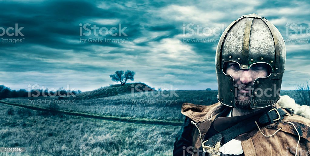 Warrior wears metal helmet and stands outside ready for battle stock photo