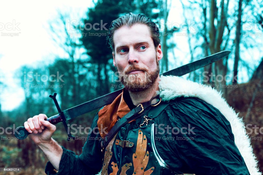 Warrior with beard holds on to sword stock photo