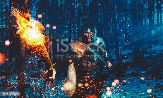 Male hunter is armed with sword and a flaming torch as he walks through a forest at night.