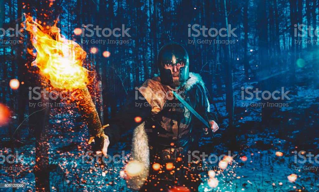 Warrior with flaming torch walks through forest at nigth ready to attack stock photo