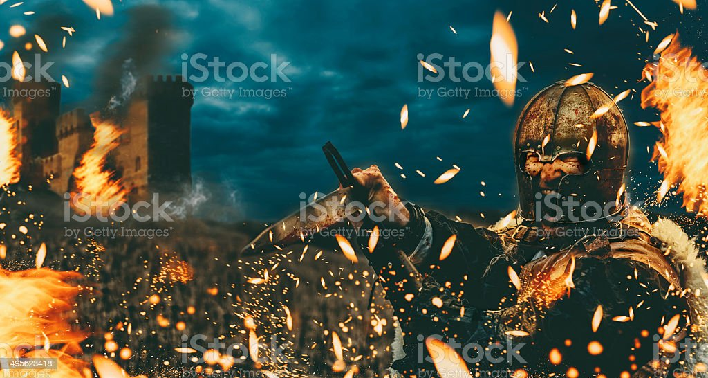 Warrior with sword attacks during a fire stock photo