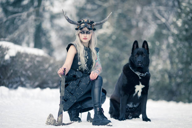 warrior woman in image of viking with ax and horned helmet next to the big black dog in winter forest. - warrior person stock pictures, royalty-free photos & images