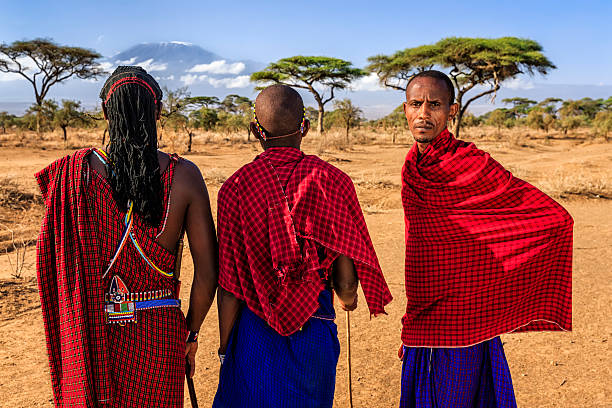 warriors from maasai tribe looking at mount kilimanjaro, kenya, africa - kenyan culture stock photos and pictures