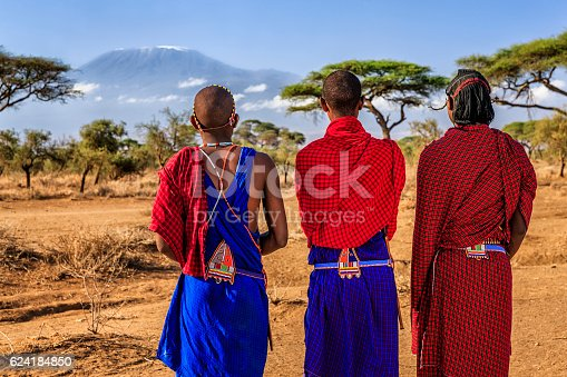 African warriors from Maasai tribe, Mount Kilimanjaro on the background, central Kenya, Africa. Maasai tribe inhabiting southern Kenya and northern Tanzania, and they are related to the Samburu.
